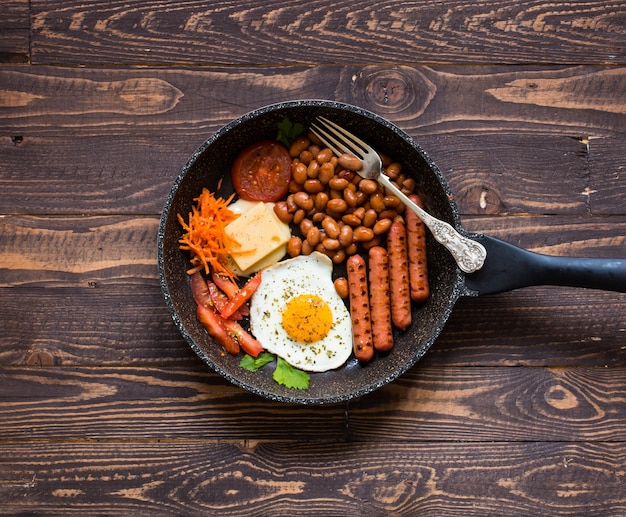 Café da manhã inglês. ovos fritos, salsichas, feijões, torradas de pão, tomate