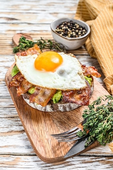 Café da manhã inglês, torradas com bacon, abacate e ovo em uma tábua de cortar. comida saudável. fundo de madeira branco. vista do topo.