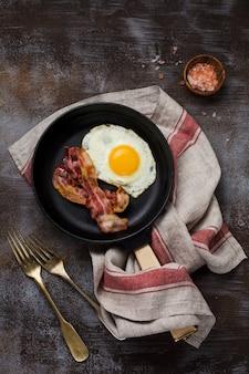 Café da manhã inglês tradicional com ovos fritos e bacon em uma panela de ferro fundido no fundo escuro de concreto. vista do topo.