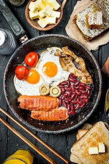 Café da manhã inglês tradicional com suco de laranja. na superfície preta rústica.