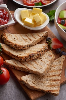 Café da manhã inglês tradicional com torradas, manteiga e geleia em uma placa de madeira.