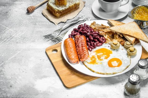 Café da manhã inglês. uma variedade de petiscos com café aromático. sobre um fundo rústico.