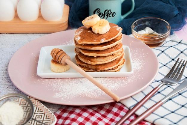 Café da manhã ingredientes receita panquecas de banana caseiras com mel panquecas na mesa da cozinha