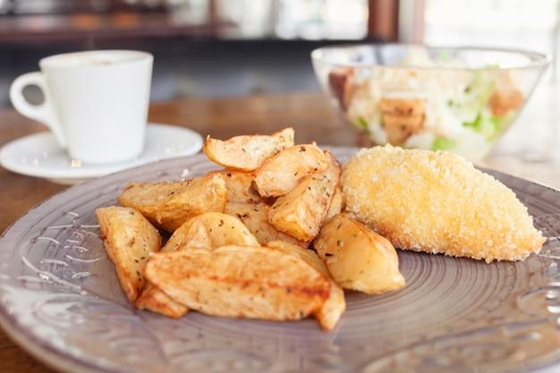 Café da manhã, jantar, almoço em um restaurante, cafeteria. batatas assadas com almôndegas, salada caesar, café americano