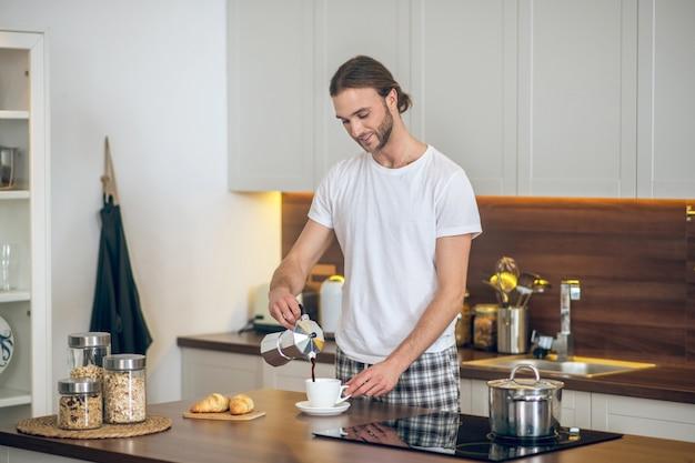 Café da manhã. jovem em casa a preparar o pequeno-almoço na cozinha