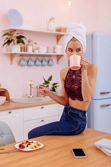 Café da manhã. jovem empresária ocupada usando jeans e sutiã tomando café da manhã em casa