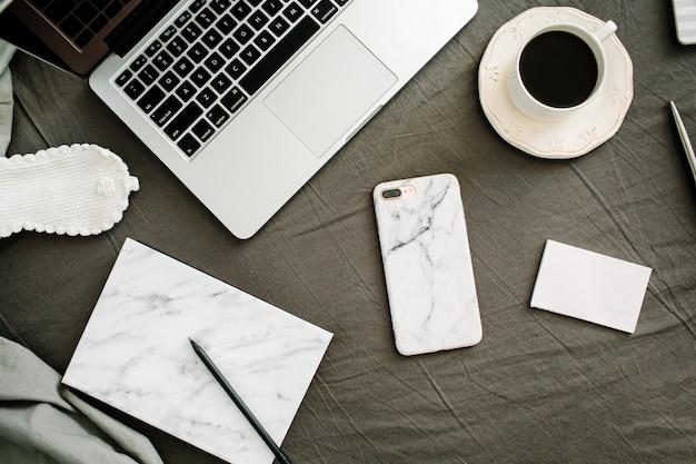 Café da manhã, laptop, diário de mármore, óculos na cama com lençol cinza e travesseiros