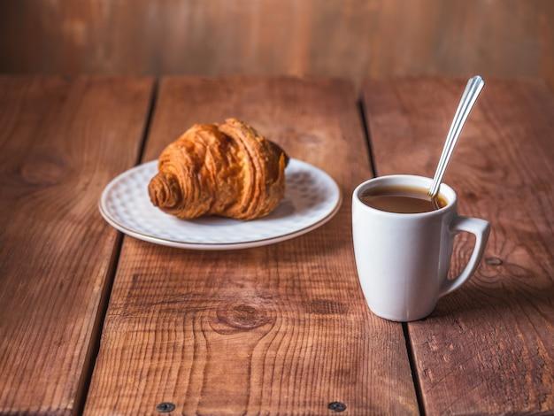 Café da manhã leve com croissant e café preto em uma caneca branca com uma colher na mesa