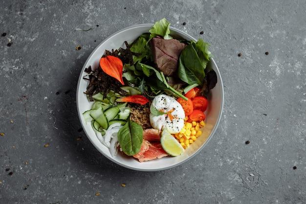 Café da manhã leve e saudável, almoço de negócios. café da manhã com ovo escalfado, trigo sarraceno, peixe vermelho, salada fresca, pepino, conceito de almoço de negócios