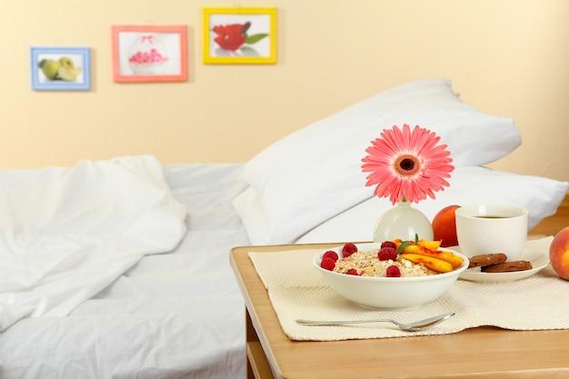 Café da manhã leve na mesa de cabeceira ao lado da cama
