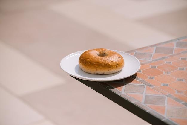 Café da manhã manhã ensolarado clima quente com donut na chapa branca no fundo da mesa. bom humor visualização horizontal