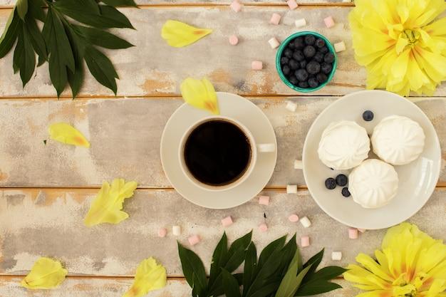 Café da manhã, marshmallows e lindas flores de peônia amarela
