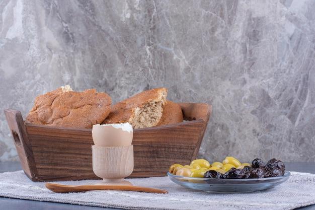Café da manhã modesto com pão, ovo e azeitonas em superfície de mármore