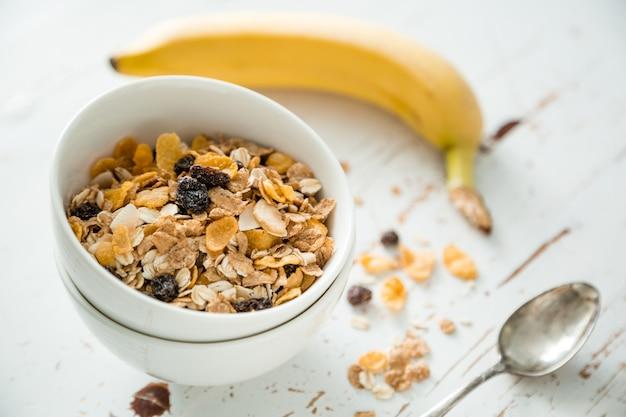 Café da manhã - muesli e frutas na mesa branca