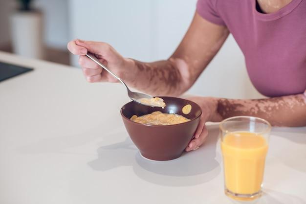 Café da manhã. mulher jovem de pele escura tomando café da manhã em casa