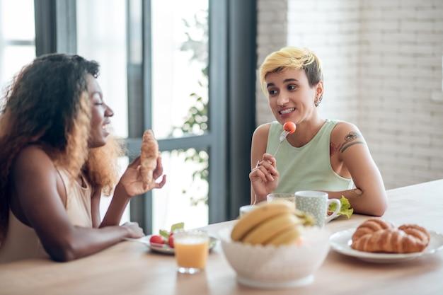 Cafe da manha. mulher jovem muito sorridente com penteado curto e tatuagem segurando um tomate e uma namorada morena com croissant