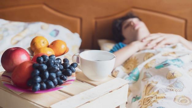 Café da manhã na bandeja de madeira na cama do hotel ao lado da pessoa adormecida