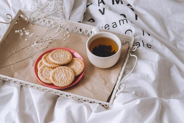Café da manhã na cama. cama branca, uma bandeja com chá e biscoitos. manhã em casa