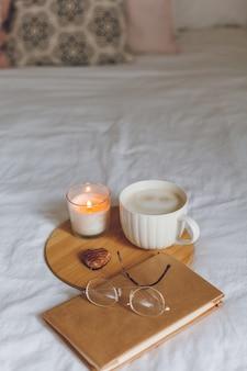 Café da manhã na cama. caneca de café, biscoitos em forma de coração, livro, copos, vela, bandeja de madeira. dia da mulher. aconchegante.