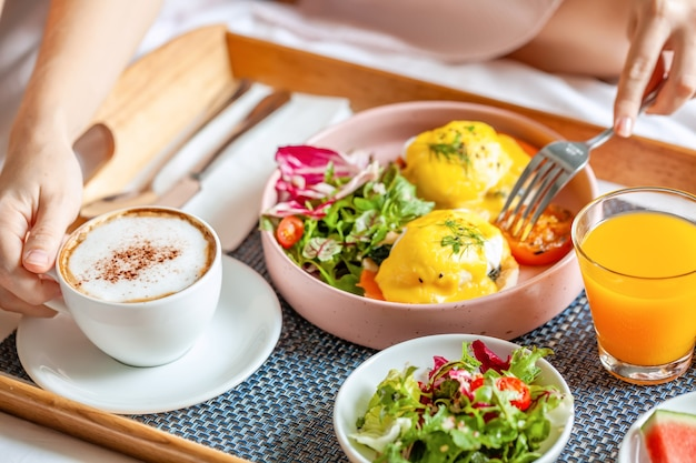 Café da manhã na cama com café, suco de laranja, salada, frutas e ovos benedict