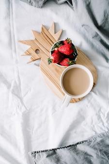 Café da manhã na cama com caneca de café e morango. lençóis cinzentos brilhantes. camada plana, vista superior.