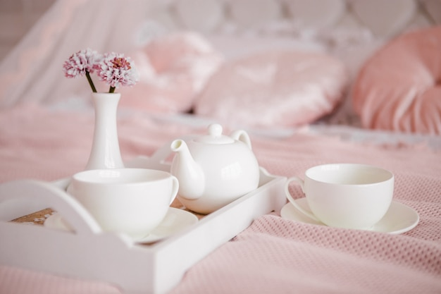 Café da manhã na cama com flores e xícaras brancas.