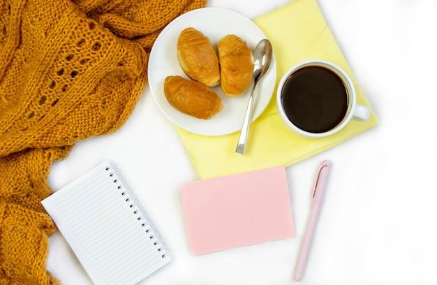 Café da manhã na cama. composição plana com café, croissants e um caderno para escrever. quadro de estilo de vida. vista superior em folhas