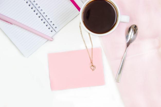Café da manhã na cama. composição plana com café, croissants e um caderno para escrever.