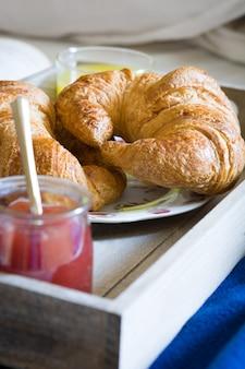 Café da manhã na cama dentro de um quarto com croissant