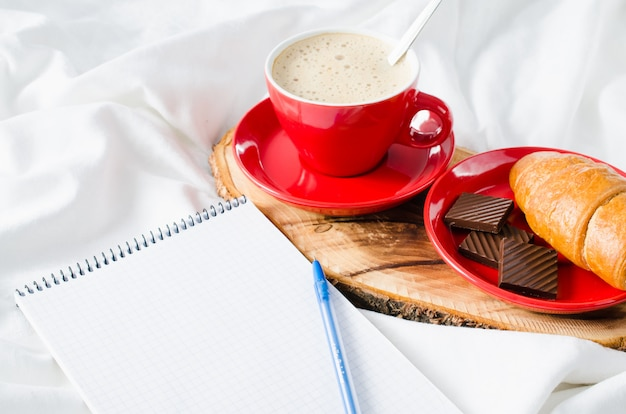 Café da manhã na cama e caderno vazio para a nota.