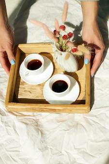 Café da manhã na cama, mãos femininas colocam experimenta com duas xícaras de café e flores ao sol em casa, camareira trazendo bandeja com café da manhã no quarto do hotel, bom atendimento
