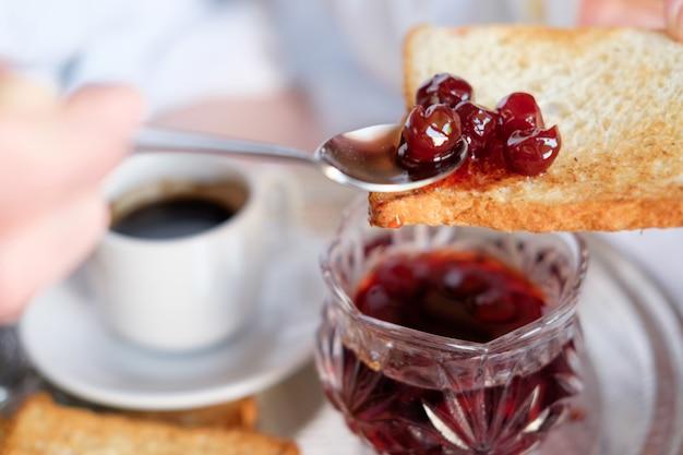 Café da manhã na cama no hotel. mão de mulher espalhando geléia de cereja em um brinde.