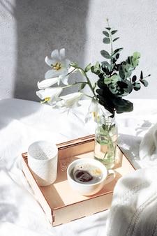 Café da manhã na cama. uma bandeja com um buquê de flores e café em uma cama branca.