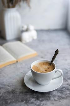 Café da manhã na mesa de concreto com livro aberto e café