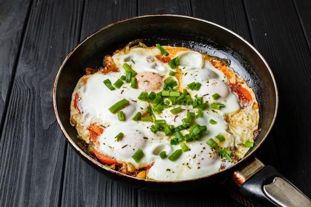 Café da manhã na mesa de madeira: um ovo frito na frigideira