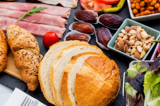 Café da manhã na mesa. pão de croissant, cereal de croissant, bacon, presunto, queijo, alface, feijão, flocos de milho, frutas, café, chá e suco de laranja é o café da manhã. , almoço ou jantar todos os dias