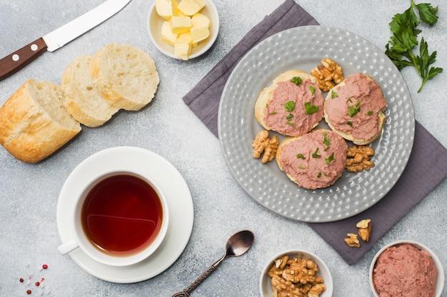 Café da manhã na mesa. sanduíches de patê de frango e manteiga. copo de chá