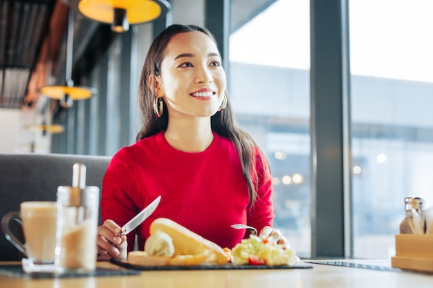 Café da manhã no café. perto de uma mulher atraente e radiante, vestindo um suéter vermelho, tomando café da manhã em um café