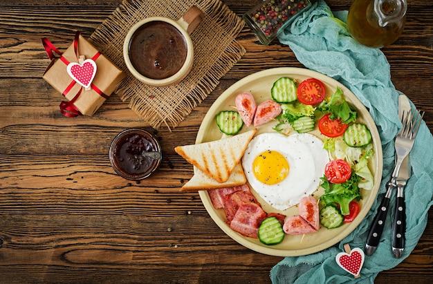 Café da manhã no dia dos namorados - ovo frito em forma de um coração, torradas, salsicha, bacon