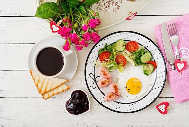 Café da manhã no dia dos namorados - ovo frito em forma de um coração, torradas, salsicha