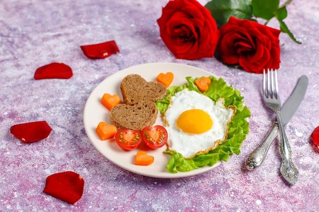 Café da manhã no dia dos namorados - ovos fritos e pão em forma de coração e vegetais frescos.