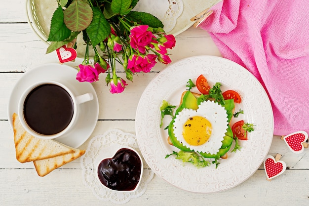 Café da manhã no dia dos namorados - sanduíche de ovo frito em forma de coração, abacate e legumes frescos. xícara de café. café da manhã inglês. vista do topo