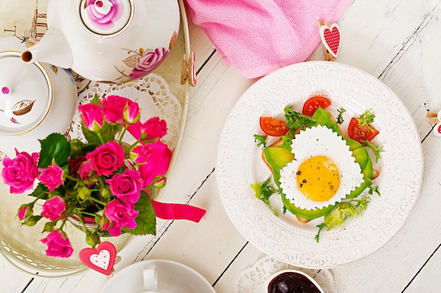 Café da manhã no dia dos namorados - sanduíche de ovo frito na forma de um coração, abacate