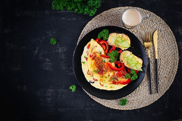 Café da manhã. omelete com colorau, queijo e tomate com sanduíches na placa preta. frittata - omelete italiana. vista superior, acima