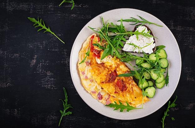 Café da manhã. omelete com tomate, queijo e salada na chapa branca. frittata - omelete italiana. vista superior, configuração plana