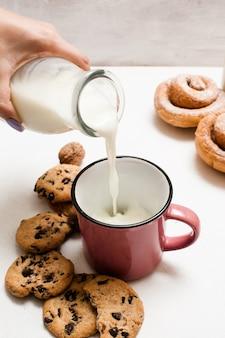 Café da manhã orgânico de pastelaria com leite e scones, close up. mulher servindo lacto fresco em um copo perto de biscoitos integrais e pãezinhos assados na mesa branca