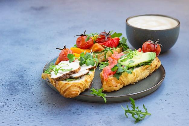 Café da manhã ou almoço com café e diferentes sanduíches de croissant