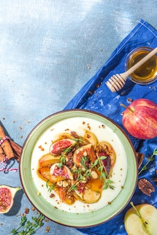 Café da manhã ou lanche de outono, mingau de semolina picante com maçãs caramelizadas, pêssego grelhado, ameixas e figos, nozes, tomilho, mel. vista superior em mesa de concreto iluminada pelo sol azul