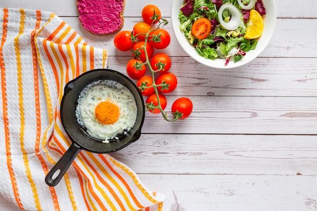 Café da manhã, ovo frito em uma panela de ferro fundido com saladeira, pasta de beterraba e tomates cereja