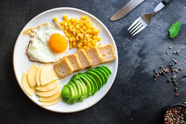 Café da manhã ovo frito pão torrado vegetais, milho, queijo e mais na mesa servindo lanche saudável